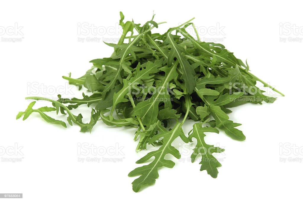 A fresh pile of rucola leaves on a white background royalty-free stock photo