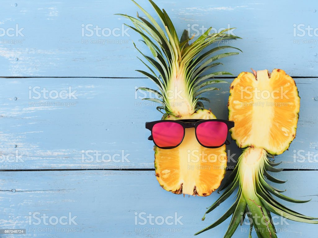 fresh pineapple and sunglasses on blue wooden table. stock photo