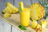 Fresh pineapple juice in the glass with fresh pineapple on wooden table.