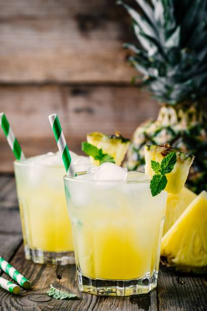 Fresh pineapple juice in two glasses with ice and mint on dark rustic background stock photo