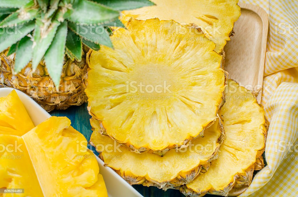 Fresh pineapple with slices on the wood texture background