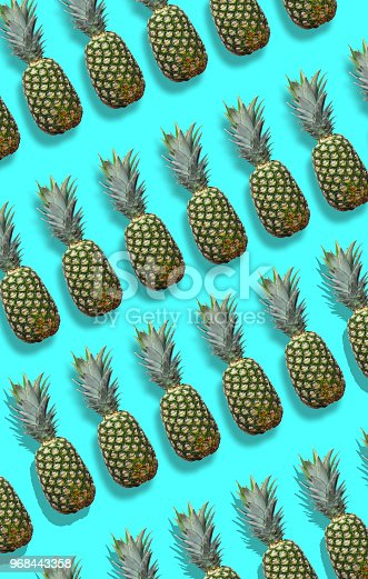 917861766istockphoto Fresh pineapples on the blue colorfurful background 968443358