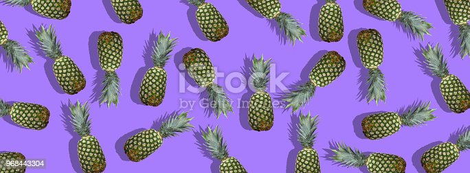 917861766istockphoto Fresh pineapples on the violet colorfurful background 968443304