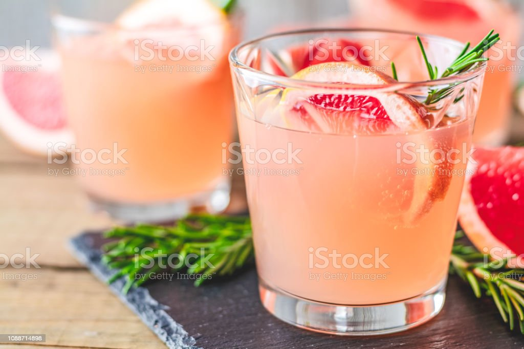 Fresh pink alcoholic cocktail with grapefruit, ice and rosemary stock photo