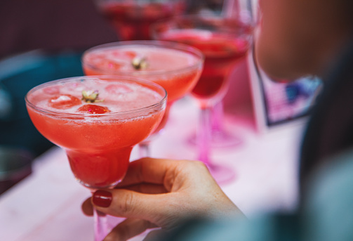 A female hand holding pink alcoholic strawberry cocktail drink with gin, lemonade, champagne or vodka in drink glass for summer drinks