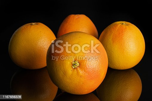 istock Fresh pink grapefruit isolated on black glass 1167656328