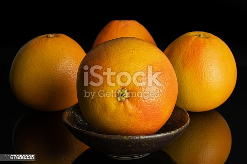 istock Fresh pink grapefruit isolated on black glass 1167656335