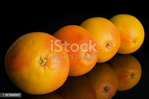 istock Fresh pink grapefruit isolated on black glass 1167656337