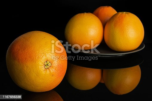 istock Fresh pink grapefruit isolated on black glass 1167656338