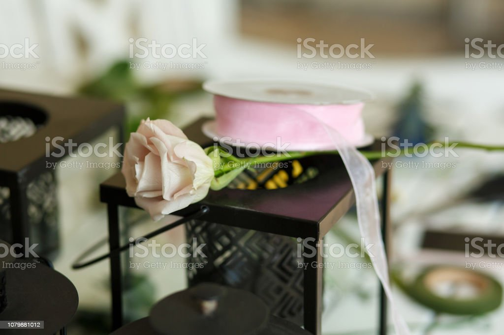 Fresh pink rose flower on decorative candle holder box. Wedding...