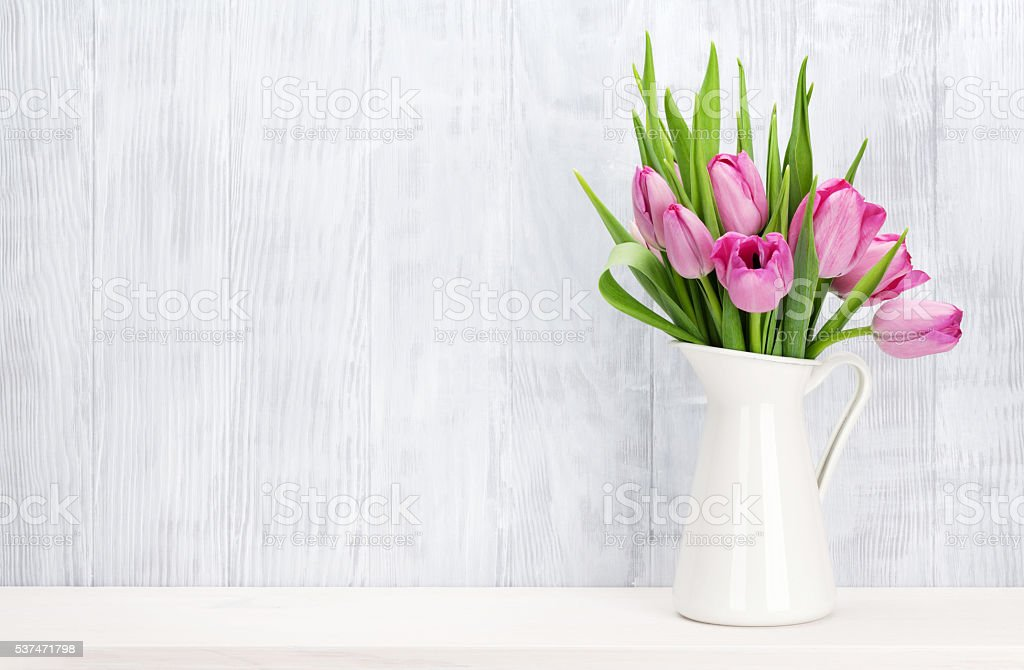 Fresh pink tulip flowers bouquet on shelf in front of wooden wall....