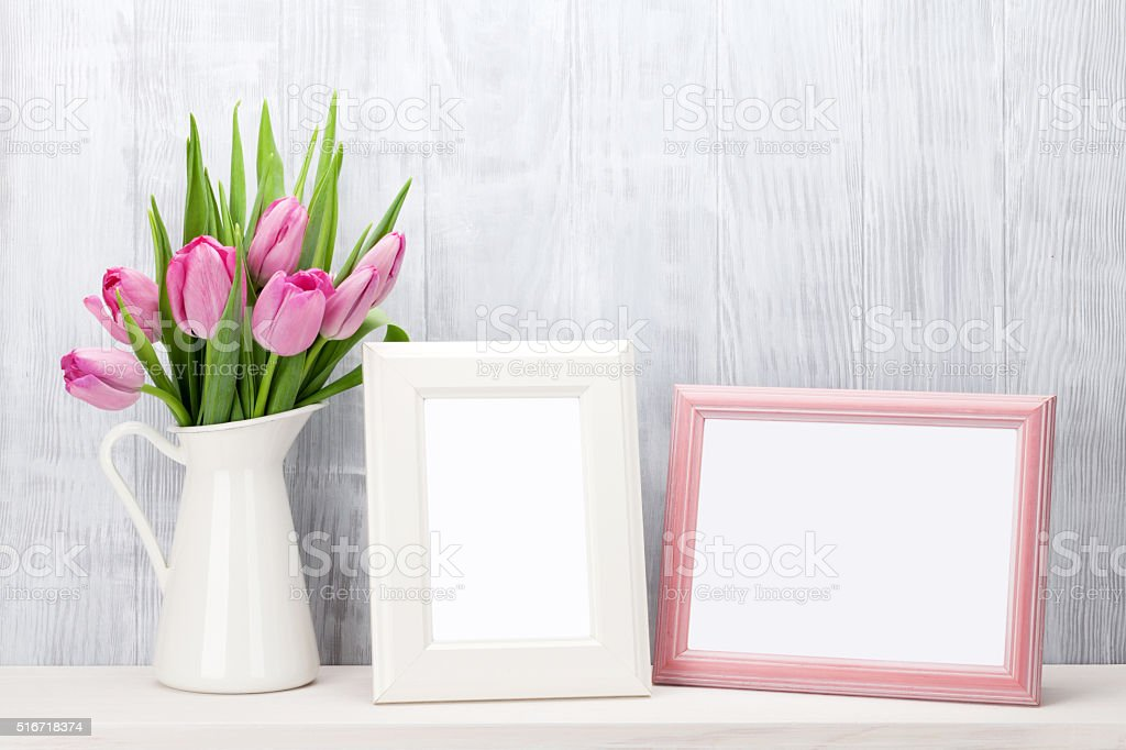 Fresh pink tulips bouquet and photo frames stock photo