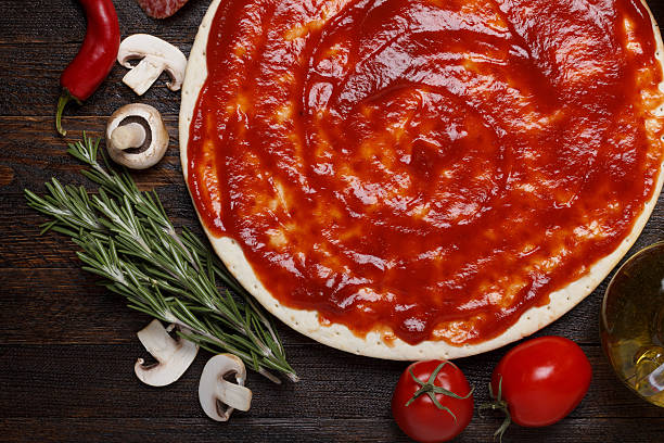 Fresh pizza dough with tomato sauce