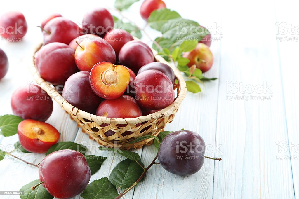 Fresh plums on a white wooden table stock photo