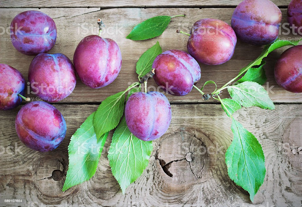 fresh plums on wooden table stock photo