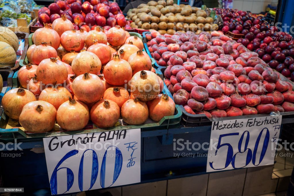 Fresh pomegranates and peaches in a food market. stock photo