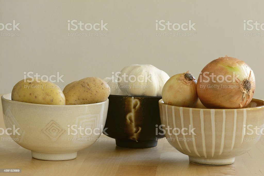 Fresh potatoes, garlic, and onions in the bowls royalty-free stock photo