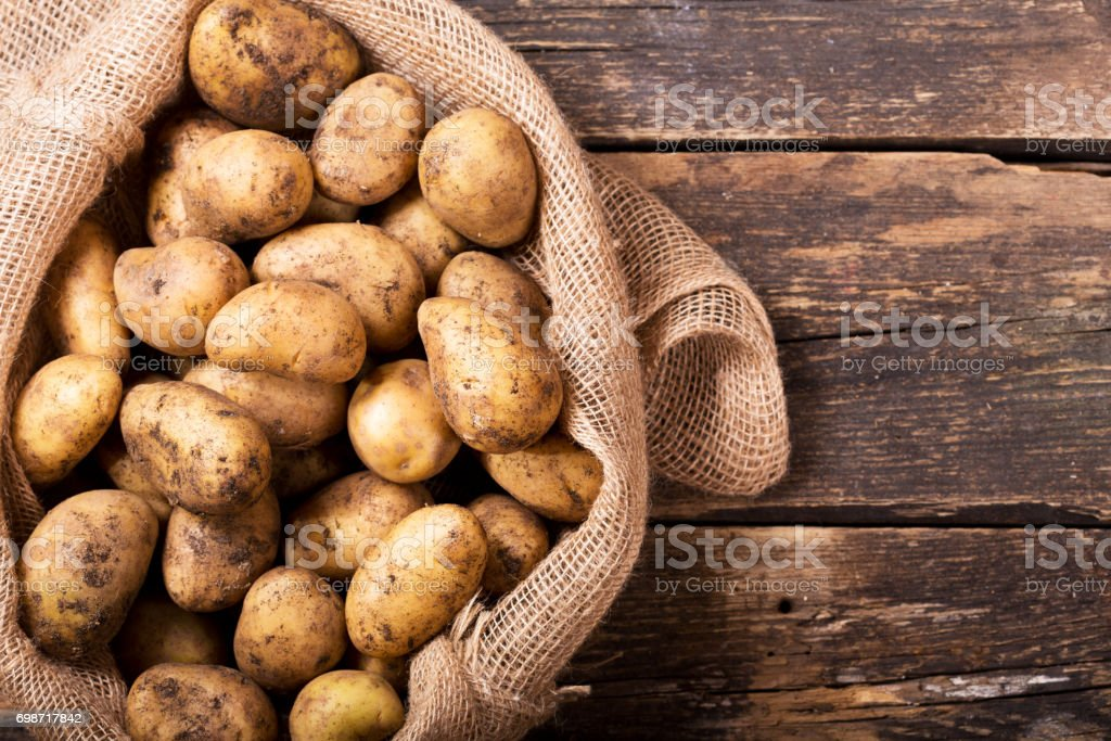 batatas frescas no saco na mesa de madeira - foto de acervo