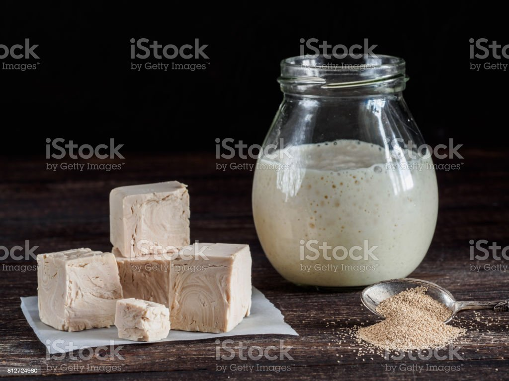 Fresh pressed yeast, dry instant yeast and active wheat sourdough starter on wooden table stock photo