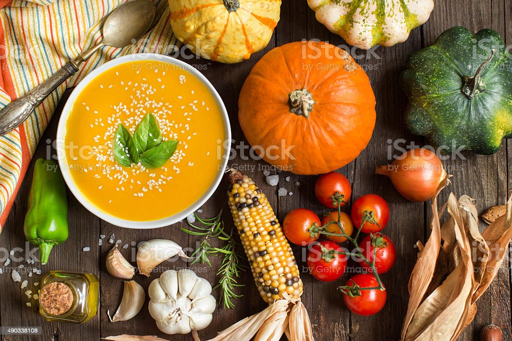 Fresh pumpkin soup and vegetables on a wooden table