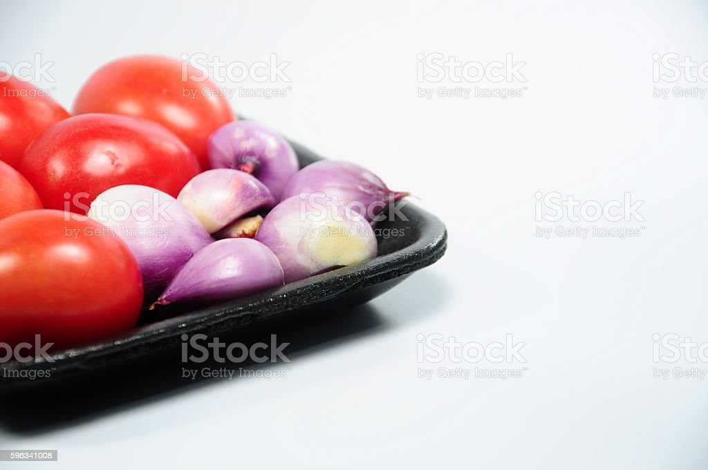 Fresh purple organic shallots and red tomatoes on black tray royalty-free stock photo
