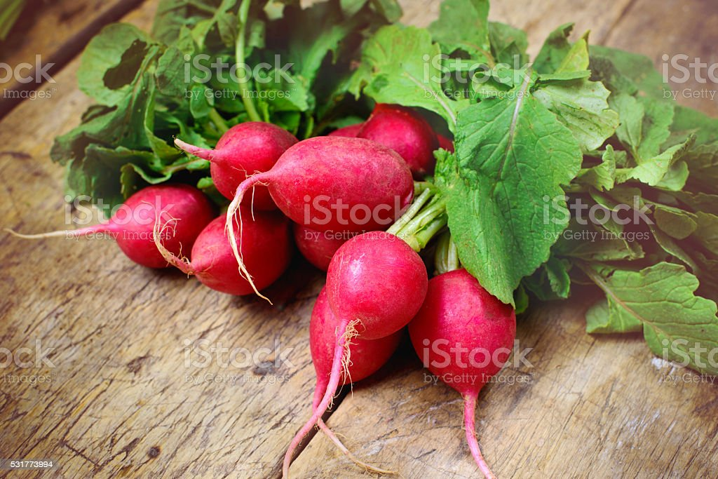 Fresh radishes on old wooden table stock photo