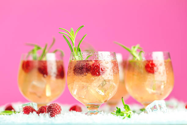 Fresh raspberry cocktail with rosemary and ice in glasses with water drops. Christmas and New Year holiday welcome drink. stock photo