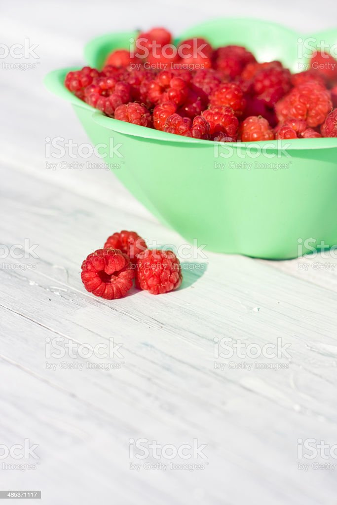 Fresh raspberry in plate on wooden rustic desk royalty-free stock photo