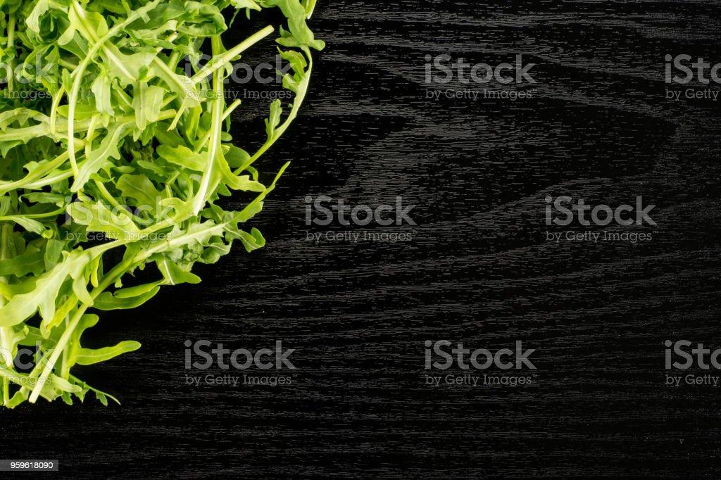 Fresco crudo rúcula (rúcula) en madera negra - Foto de stock de Alimento libre de derechos