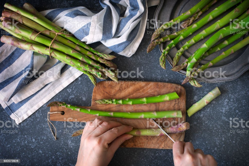 Fresh  raw asparagus on stone background. Women female hands cut asparagus on wooden cooking board. Top view royalty-free stock photo