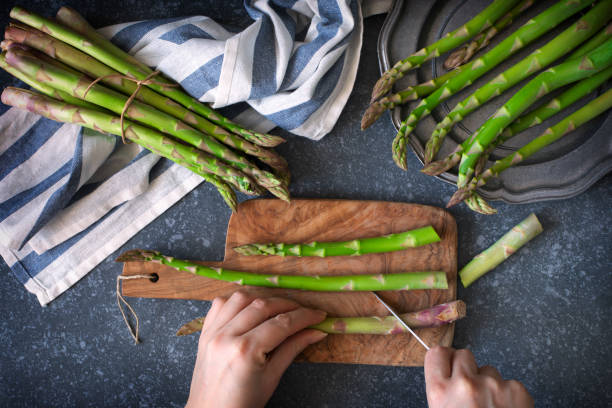 Fresh  raw asparagus on stone background. Women female hands cut asparagus on wooden cooking board. Top view stock photo