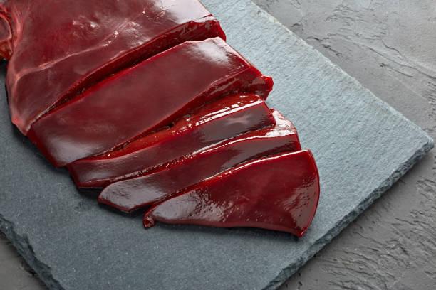 Fresh raw beef livers on a black stone cutting board  on dark background. stock photo