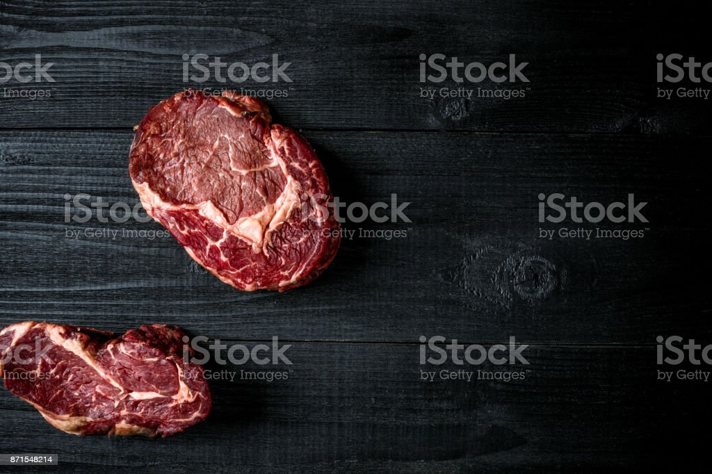 Fresh raw beef on black wooden background. Top view stock photo