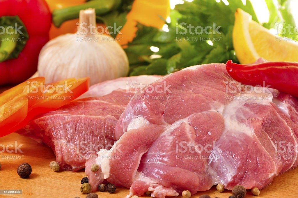 Fresh raw beef pork, meats on board with vegetables royalty-free stock photo