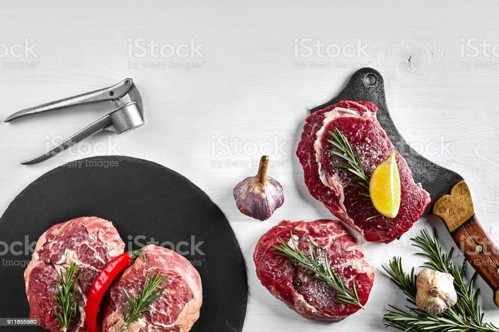 Fresh raw beef steaks with herbs, garlic, olive oil, pepper, salt and rosemary on black board: Tenderloin, Striploin, Rib Eye stock photo