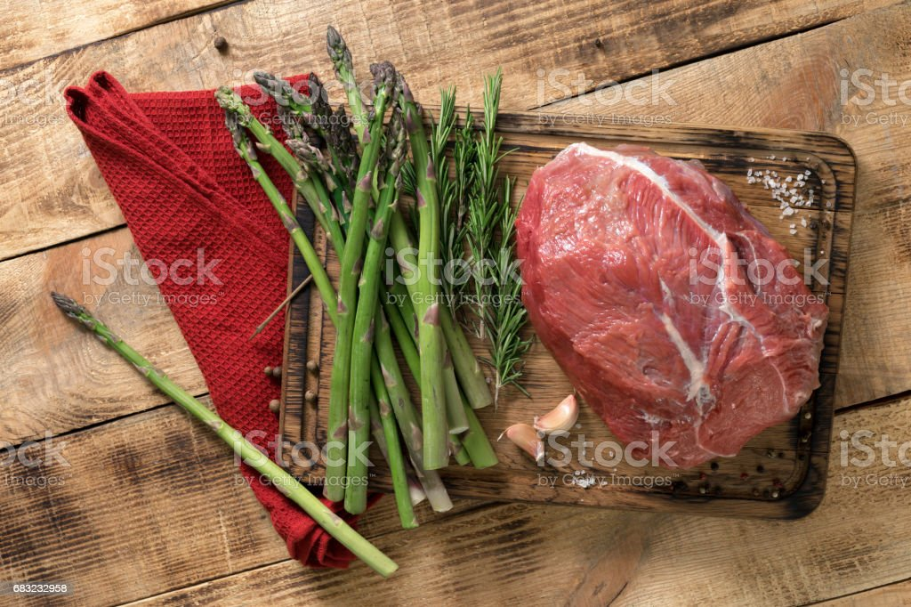 Fresh raw beef tenderloin with rosemary and asparagus on a wooden table, top view royalty-free 스톡 사진