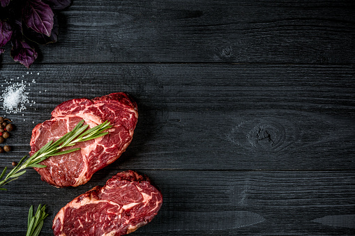 Fresh raw beef with basil and a sprig of rosemary on black wooden background