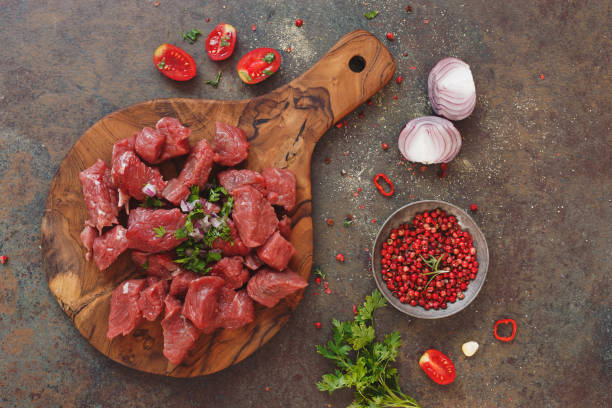 Fresh raw chopped angus beef on a wooden cutting board Fresh raw chopped angus beef on a wooden cutting board with spices, herbs and vegetables, stone background, top view beef stew stock pictures, royalty-free photos & images