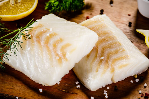 fresh raw cod fillet on cutting board - cod imagens e fotografias de stock