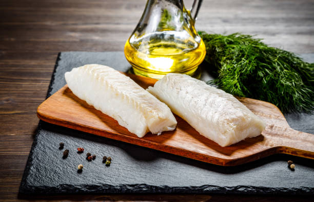 fresh raw cod fillet on cutting board - cortado em filete imagens e fotografias de stock