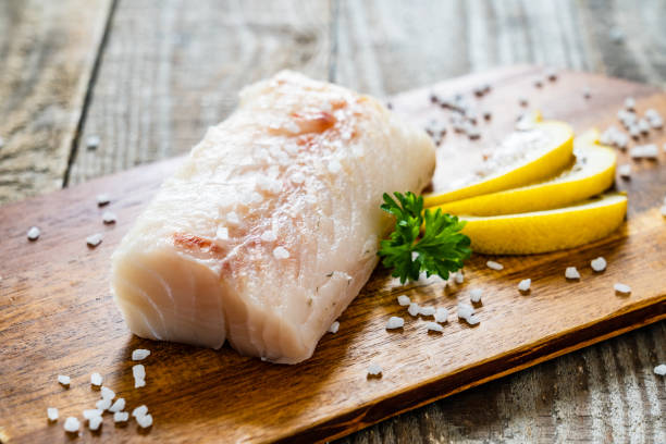 Fresh raw cod fillet on cutting board stock photo