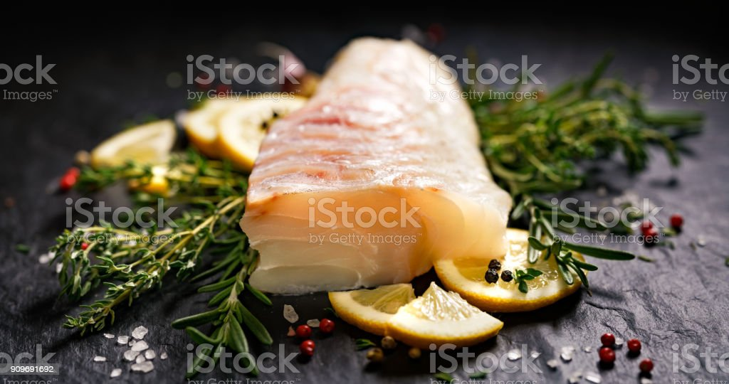 Fresh raw cod fillet with addition of herbs and lemon slices stock photo