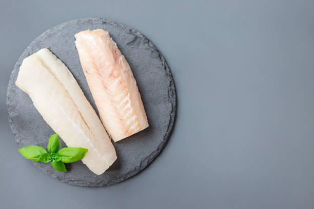 Fresh raw cod fillet with basil on stone plate, horizontal, copy space, top view stock photo
