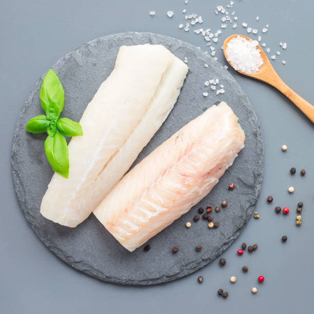 Fresh raw cod fillet with spices, pepper, salt, basil on a stone plate, top view, square format stock photo