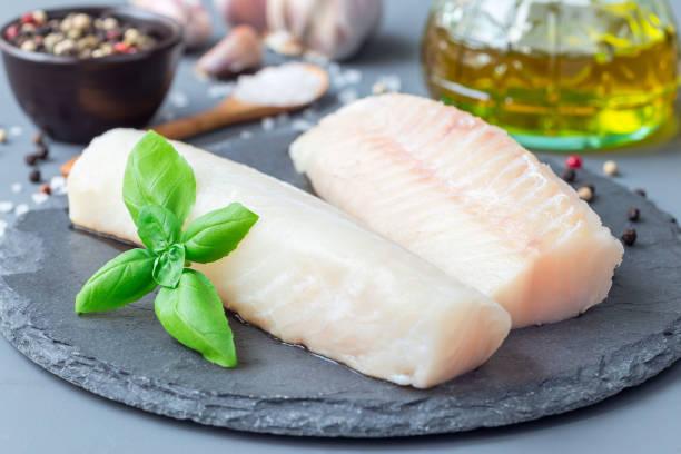 fresh raw cod fillet with spices, pepper, salt, basil on stone plate, horizontal - cod imagens e fotografias de stock