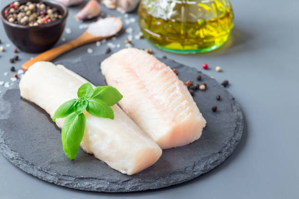 Fresh raw cod fillet with spices, pepper, salt, basil on stone plate, horizontal, copy space stock photo