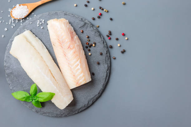 Fresh raw cod fillet with spices, pepper, salt, basil on stone plate, horizontal, copy space, top view stock photo