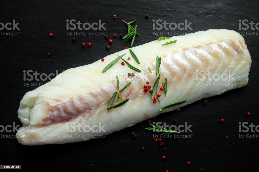 Fresh Raw Cod loin fillet with rosemary, cracked pepper on stone board stock photo