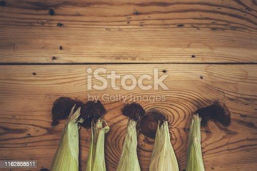 Fresh raw corn cobs on wooden background. Raw corn with skin. Sweet corn