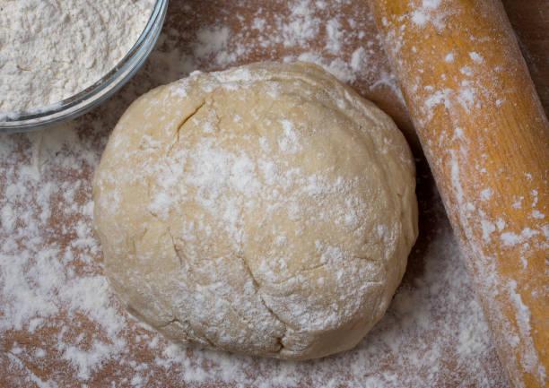 Frischer Rohteig für Pizza oder Brotbacken auf Holzschneidebrett. – Foto